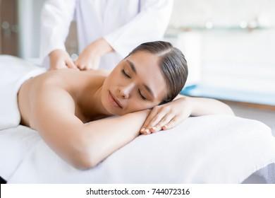 Serene female lying in spa salon and having her back massaged