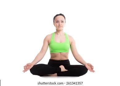 Serene fitness girl does yoga training, sitting in Ardha Padmasana, half lotus posture, Siddhasana, Accomplished Pose, asana for meditation, breathing exercises