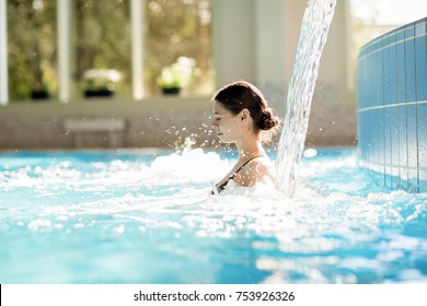 Serene girl enjoying stream of waterfall and its gentle splashes in swimming-pool at spa resort