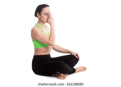 Serene girl practicing yoga nadi shodhana pranayama (Alternate Nostril Breathing), sitting in Easy (Decent, Pleasant Pose), Sukhasana, meditation, copy space