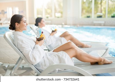 Serene girls in white bathrobes lying on deckchairs by swimming-pool and enjoying pinacolada from coconuts