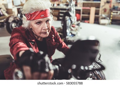 Serene grandmother driving motorcycle from garage
