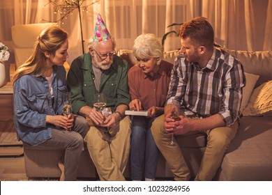Serene granny pointing finger on frame while sitting near grandfather, female and man on sofa. Memory concept