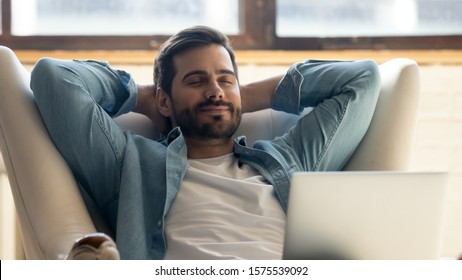 Serene happy healthy young man relaxing on comfortable armchair with laptop, smiling calm relaxed guy lounge eyes closed in sunny cozy home with notebook device enjoying lazy leisure lifestyle on - Shutterstock ID 1575539092