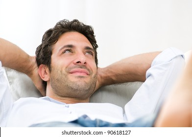 Serene happy man relaxing on sofa at home