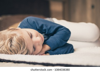 Serene kid resting on the blanket and taking a nap.