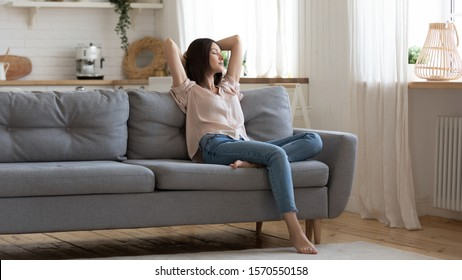 Serene lady housewife lounge sit on sofa feel fatigue napping hold hands behind head, calm young woman rest on comfort couch with eyes closed breath fresh air in cozy clean modern living room at home