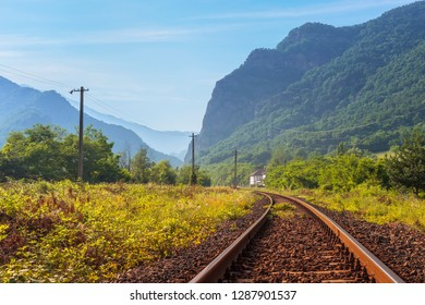 Serene landscape with rusty railway track passing through Cozia mountains along Olt river gorge in Valcea county, Romania.