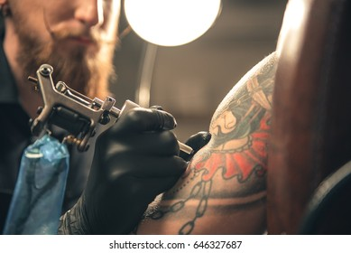 Serene male maker doing tattoo on arm of client in apartment
