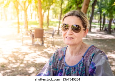 Serene mature woman enjoying the sunny day in a recreation area