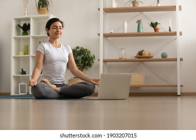 Serene millennial mixed race woman engaged in yoga practice breath deep feel comfort harmony. Tranquil inspired young indian lady sit by laptop on floor at lotus asana meditate to reach peace of mind