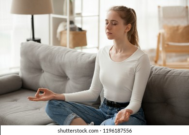 Serene millennial woman sitting on couch in living room at home. Girl take a break for meditation yoga practice. Thinking, stress relief, healthy good habits, mental health, mindful lifestyle concepts