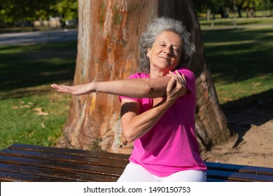 Serene old lady warming up for morning exercise in park. Senior grey haired woman in casual sitting on bench and stretching hand. Age and activity concept