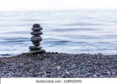 A serene rock tower scene with a calm lake in the background on a cool fall day.