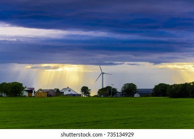 Serene Scandinavian landscape at dusk, white nights shot with blue skies and puffy clouds with wind farm.