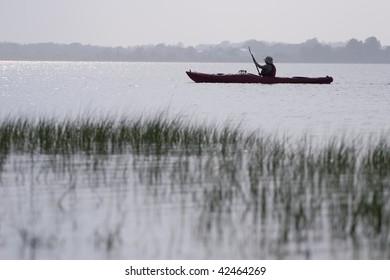 Serene scene of woman kayaking.
