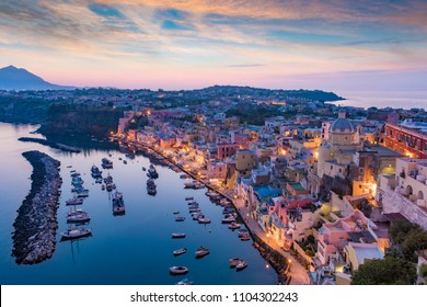 Serene sea, colorful houses on coastline, fishing and sightseeing boats in Marina Corricella in sunset time at Procida island, Italy. Procida is located between Capo Miseno and island of Ischia.