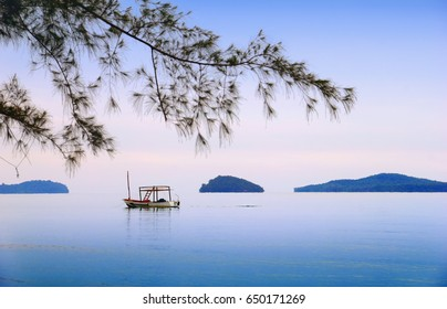 Serene sea scape, lonely traditional khmer boat, small islands in early morning mist at sun rise, blue sky, blur tree branch in Otres beach, Sihanouk ville, Gulf of Thailand, Cambodia, South East Asia