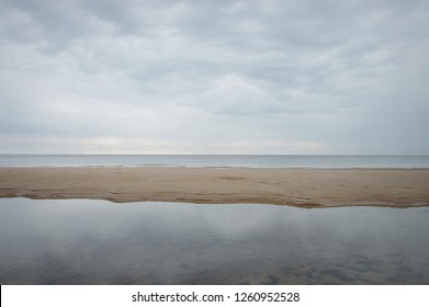 Serene seascape in minimalistic setting with a strip of land between body of water. Sky and sea the same color giving impression of abstract lines