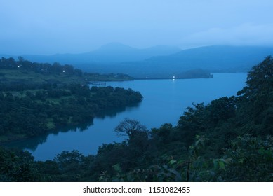 A serene tranquil and peaceful landscape at dawn with a fresh water lake know as Bhandardara surrounded by dense forest and mountains in the hazy and foggy monsoon atmosphere. Maharashtra India Asia