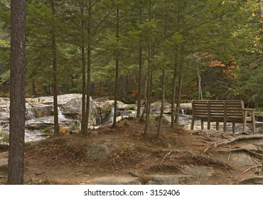 Serene waterfall in New Hampshire Mountains with a bench for rest