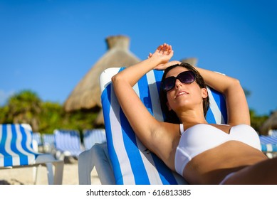 Serene woman relaxing and sunbathing at caribbean tropical resort beach. Relaxed tanned girl resting on summer vacation.