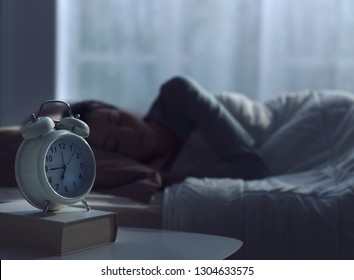 Serene woman sleeping in her bed and alarm clock in the foreground