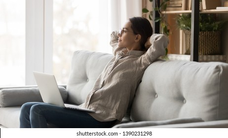 Serene woman wearing glasses casual clothes holds computer on laps leaning on couch stretching with hands behind head resting looking out the window thinking freelancer having break feels good concept