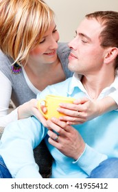 Serene young family couple drinking cup tea or coffee at home embracing in  love