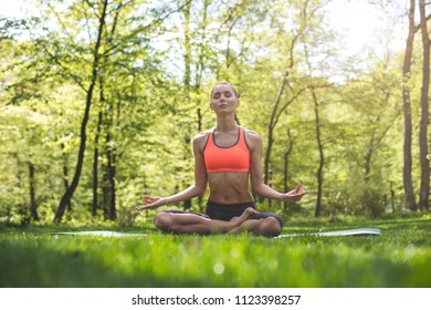 Serene young lady is enjoying solitude in green scenic area. She is sitting in lotus asana on mat among grass and closing eyes for concentration on thoughts. Meditating outdoors concept