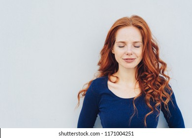 Serene young redhead woman taking a moment to relax or meditate standing with closed eyes against a white wall with copy space