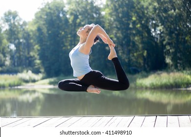 Serene young sporty beautiful woman floating in midair during yoga practice, levitating above ground in EkaPada Radjakapotasana (One-Legged King Pigeon Posture), working out outdoors in park