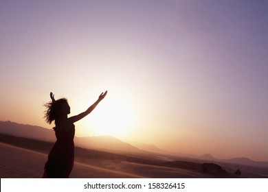 Serene young woman with arms outstretched doing yoga in the desert