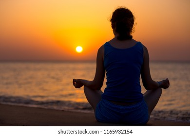 Serene young woman doing yoga training on the beach, Sitting in Easy (Pleasant Pose), Sukhasana, meditating, relaxing at sunset or sunrise, back view