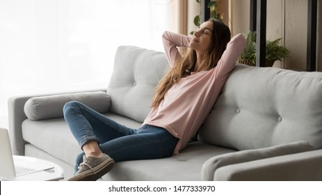 Serene young woman pretty relaxing on couch in living room. Calm female freelancer crossing hands behind head, closing eyes and taking a break during remote work day at home, stress free concept.