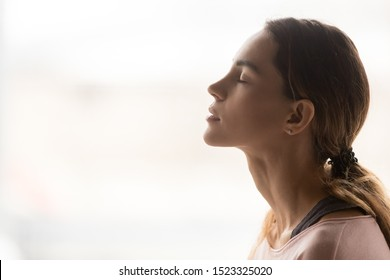 Serene young woman taking deep breath of fresh air relaxing meditating with eyes closed enjoying peace, calm girl tranquil face doing yoga pranayama exercise feel no stress free relief, side view