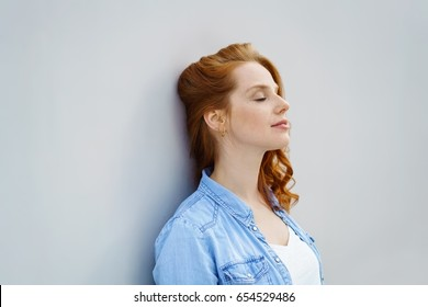 Serene young woman taking a moment to relax leaning back against an interior white wall with her eyes closed and a calm expression