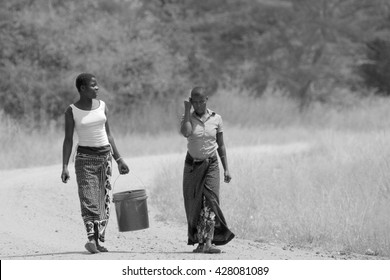 SERENGETI NATIONAL PARK, TANZANIA - JUNE 11: women bringing a bucket of water on June 11, 2013 in Serengeti National Park. Millions of people in Tanzania don't have access to safe water