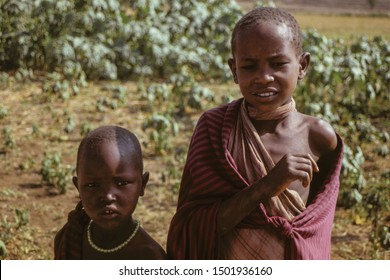 Serengeti, Tanzania - February 10, 1997. Curious Maasai children dressed in typical clothes in the Serengeti. A huge national park in the African savannah where several species of large mammals live.