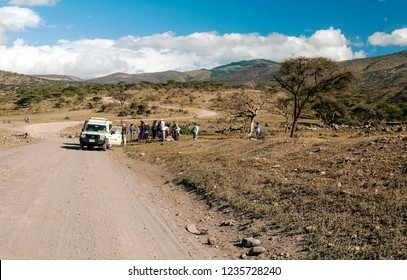 SERENGETI, TANZANIA - MAY 2014. Tourist in jeep safari in the road of National Park of Tanzania. They are traying see animals.