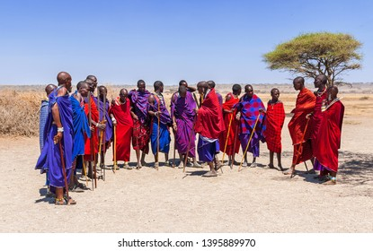 Serengeti, Tanzania - September 21. 2012: A groupd of Massai men in colorful cloth gethering together in a Massai village in the Serengeti National Park