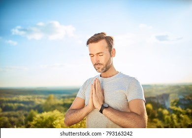 Serenity concept. Man praying or meditating outdoors