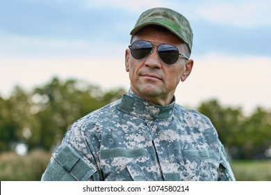 Sergeant in sunglasses. Severe serious cool soldier in spectacles and cap outdoors.