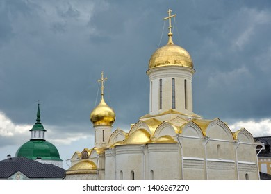 SERGIYEV POSAD, RUSSIA - Golden Domes of Trinity Cathedral Against Dark Rain Clouds. View from Cathedral Square of Holy Trinity - St. Segius Lavra (monastery).