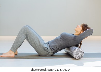 Seria photo of young caucasian female sportswoman uses a foam roller for self-massage for relaxation, stretching muscles and back pain. Girl in workout in pilates studio.
