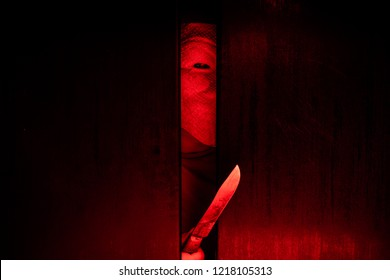 Serial killer / eye peeking behind the door with kinfe