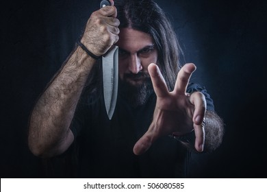 Serial killer maniac holding a knife and screaming, halloween concept
