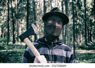 Serial maniac with axe in forest, bloody killer, murderer, mad man in scary mask with beastly grin, helloween costume, horror concept.