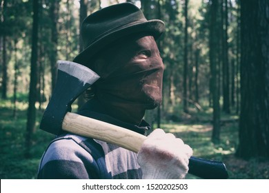 Serial maniac with axe in forest, bloody killer, murderer, mad man in scary mask and hat outdoor, helloween costume, horror concept.