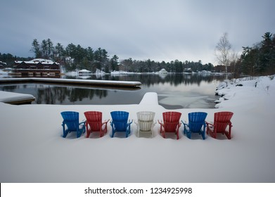 A series of Adirondack chairs covered in snow are facing calm frozen  waters in Muskoka, Ontario, Canada. The chairs are red, blue and white.